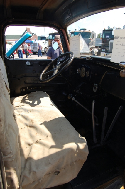 The interior of the truck – with torn canvas seat cover and lack of door panels - reflects its Depression-era working status.