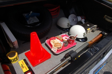 "Houts has found other items to finish the unit, including cones, police tape, a radio, helmets, and even a tray of plastic drive-in food for when he goes ""Code 7"" (on break)."